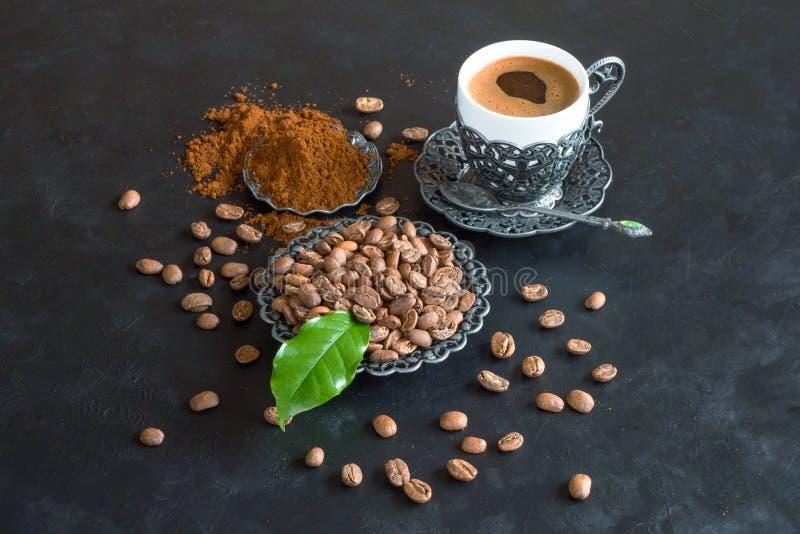 Chicchi di caffè e della tazza di caffè con polvere a terra su fondo nero fotografia stock