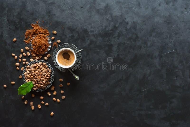 Chicchi di caffè e della tazza di caffè con polvere a terra su fondo nero, vista superiore fotografia stock