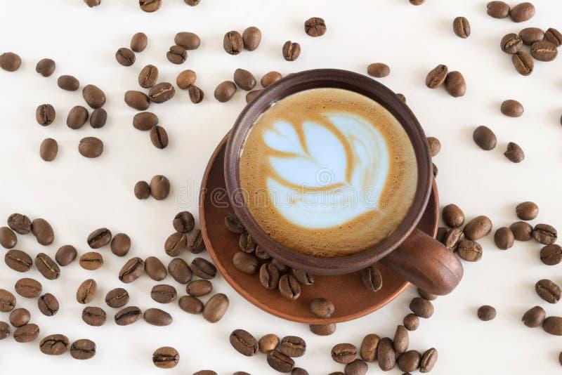 Chicchi di caffè e della tazza di caffè su un fondo bianco Vista superiore immagine stock libera da diritti