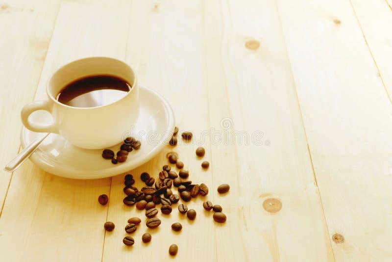 Chicchi di caffè e tazza di caffè calda su di legno fotografie stock libere da diritti