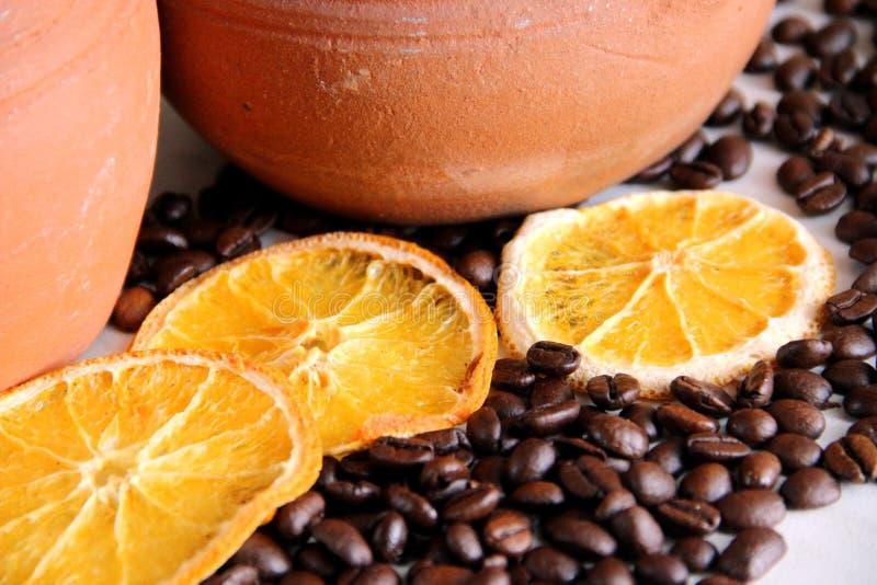 chicchi di caffè e tre pezzi di arancia secca sulla tavola sui precedenti dei piatti dell'argilla fotografia stock