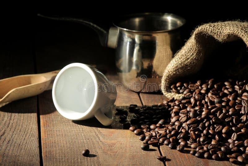 chicchi di caffè e una tazza e un cezve su una tavola di legno marrone fotografie stock