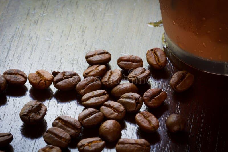 Chicchi di caffè estremi del primo piano con caffè ghiacciato in vetro di plastica, fotografia stock