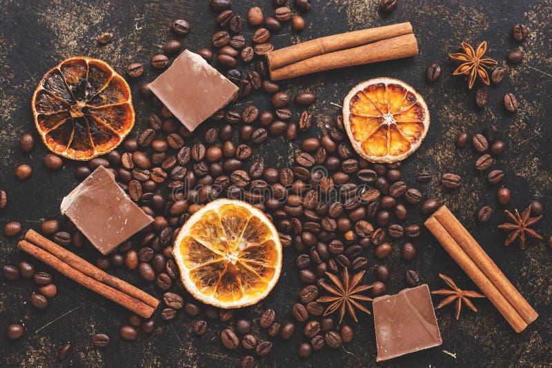 Chicchi di caffè, fette arancio, cioccolato e bastoni e anice stellato di cannella su un fondo scuro Vista superiore, disposizion immagini stock