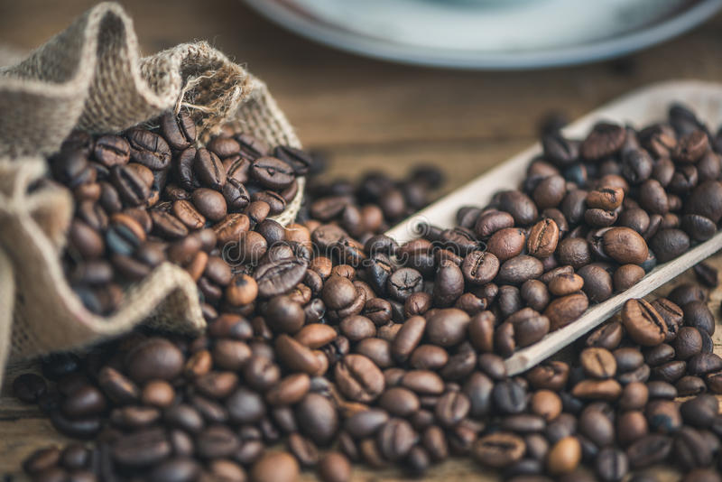 Chicchi di caffè rovesciati dal sacco della tela da imballaggio fotografie stock