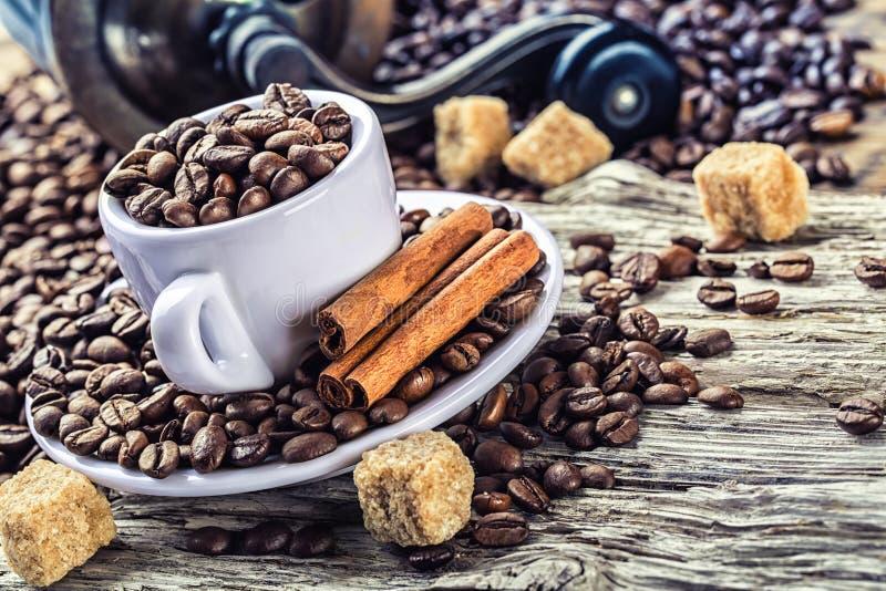 Chicchi di caffè rovesciati in tazza di caffè su una tavola di legno molto vecchia con lo zucchero di canna Nei precedenti un mac fotografia stock