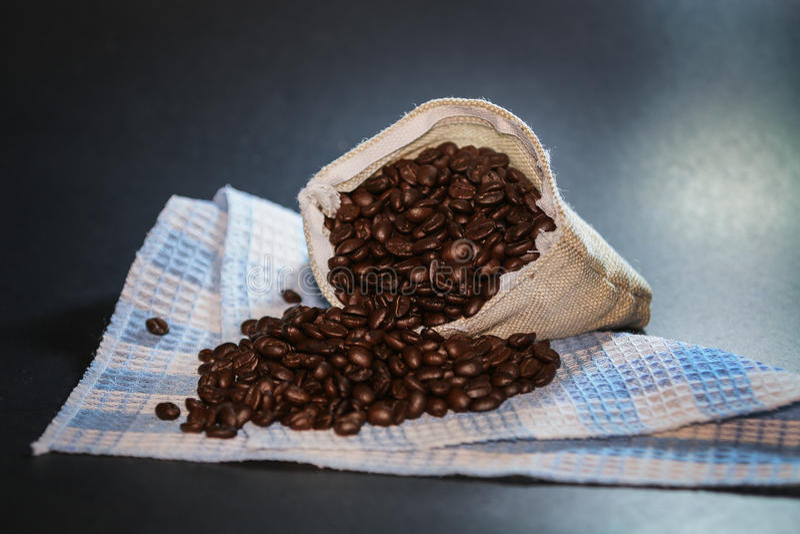 Chicchi di caffè in sacchetto Fondo leggero immagine stock