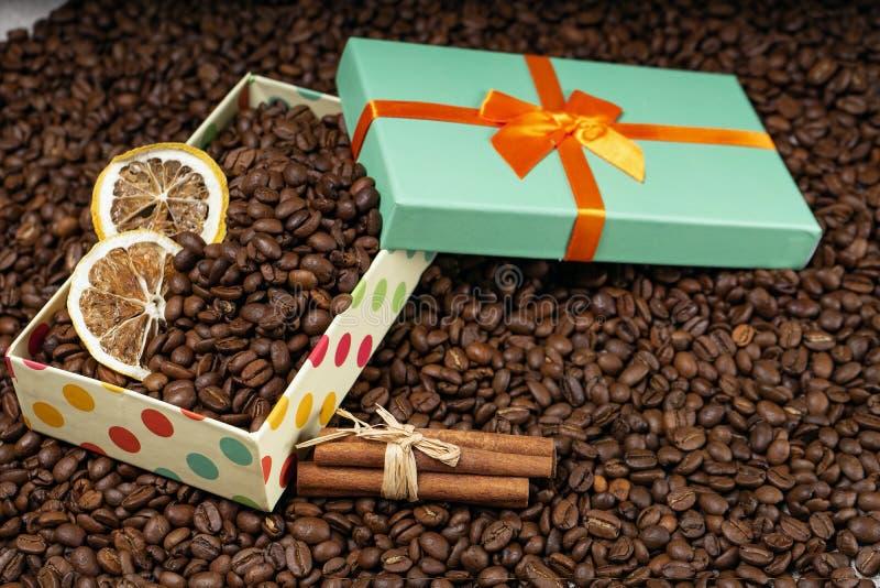 Chicchi di caffè sciolti, contenitore di regalo con i chicchi di caffè secchi del limone e bastoni di cannella Copi lo spazio immagine stock