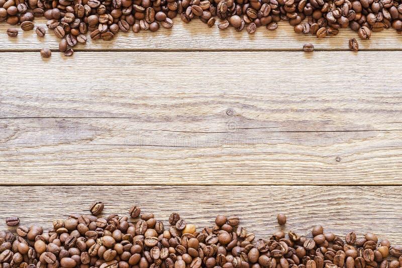 Chicchi di caffè sparsi su un fondo di legno 1 immagini stock