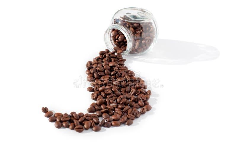 Chicchi di caffè sparsi in una bella onda dal barattolo di vetro trasparente su una fine isolata fondo bianco sulla vista superio immagine stock libera da diritti