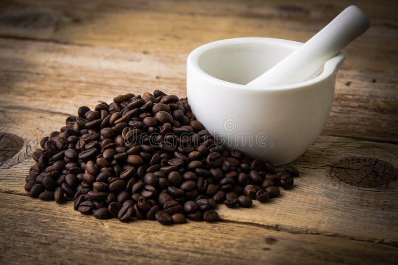 Chicchi di caffè su fondo di legno e sul mortaio bianco immagini stock