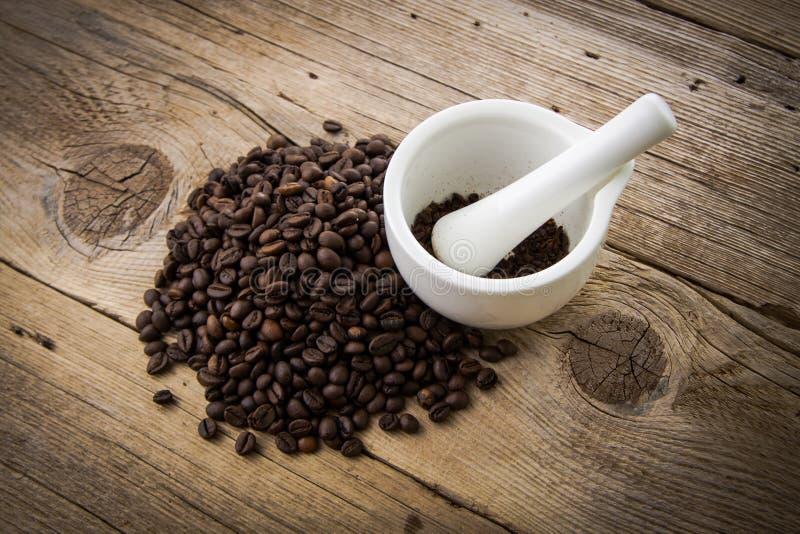 Chicchi di caffè su fondo di legno e sul mortaio bianco fotografia stock