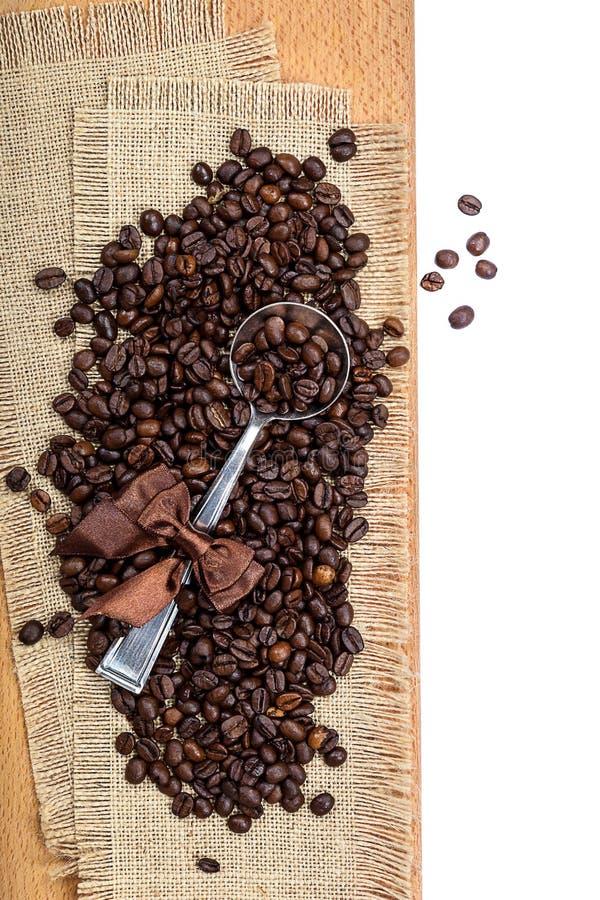 Chicchi di caffè su tela di sacco con un cucchiaio del cupronichel fotografia stock libera da diritti