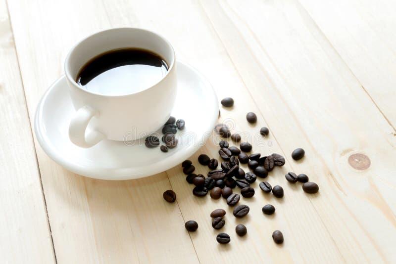 Chicchi di caffè sulla tavola di legno con caffè fotografia stock