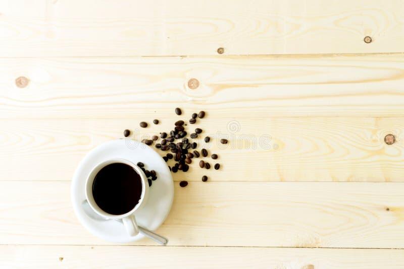 Chicchi di caffè sulla tavola di legno con la tazza da caffè immagini stock