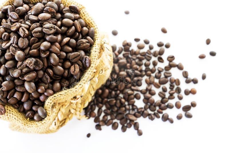 Chicchi di caffè in un sacco su un fondo bianco fotografia stock