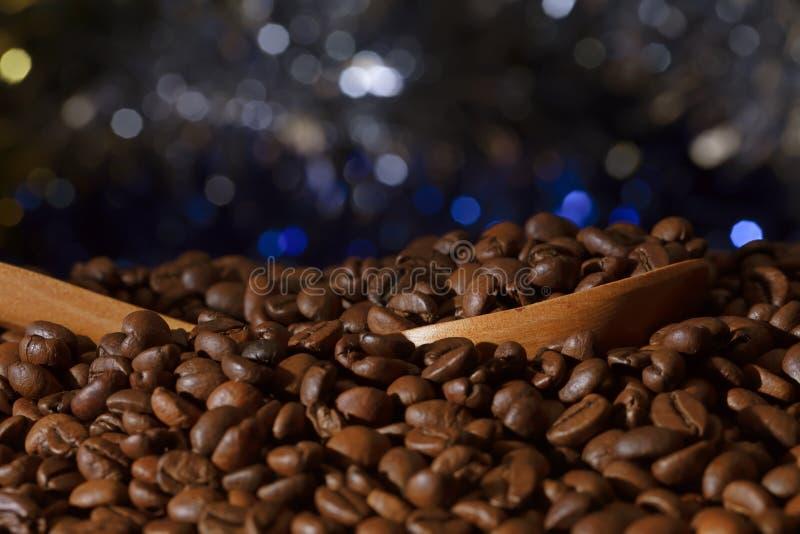 Chicchi di caff? arrostiti con una siviera di legno fotografie stock libere da diritti