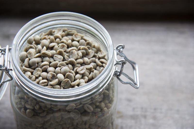 Chicchi di caff? crudi, chicchi di caff? non arrostiti in barattolo di vetro sulla tavola di legno immagine stock libera da diritti