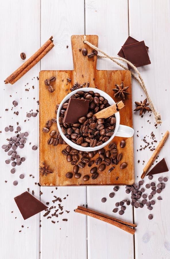 Chicchi e cioccolato di caffè sopra fondo di legno immagini stock