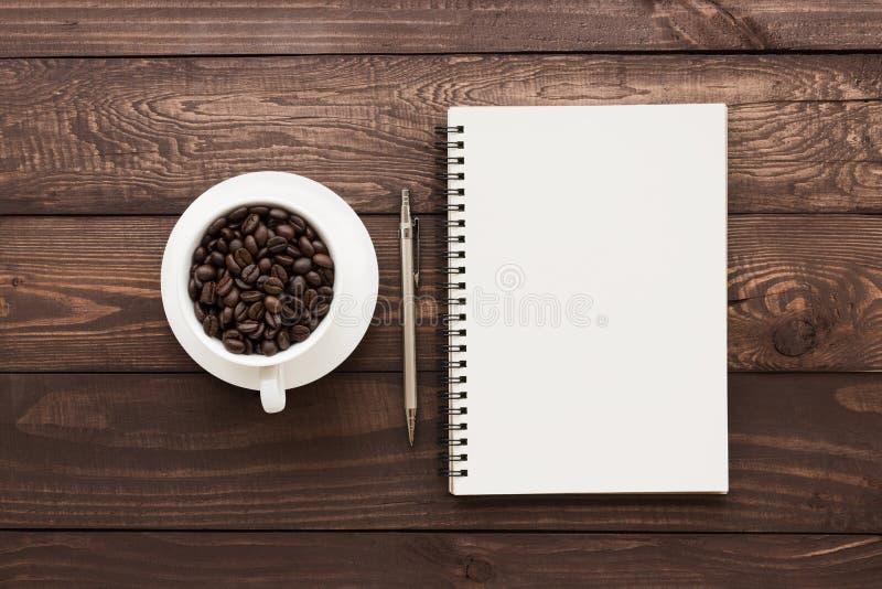 Chicco di caffè in pagina in bianco del libro e della tazza sulla tavola di legno immagini stock libere da diritti