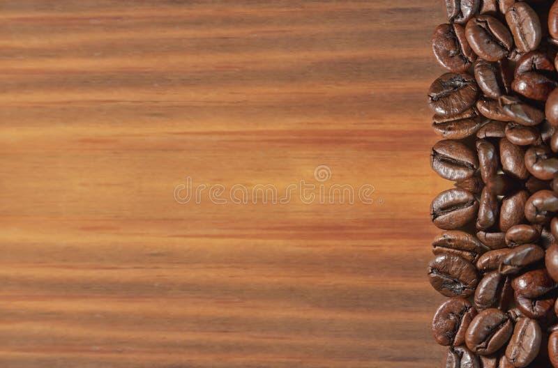Chicco di caffè su un fondo di legno marrone immagine stock