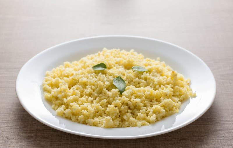 Chicco di grano cucinato del miglio sul piatto bianco e sulla tavola di legno Deta immagini stock