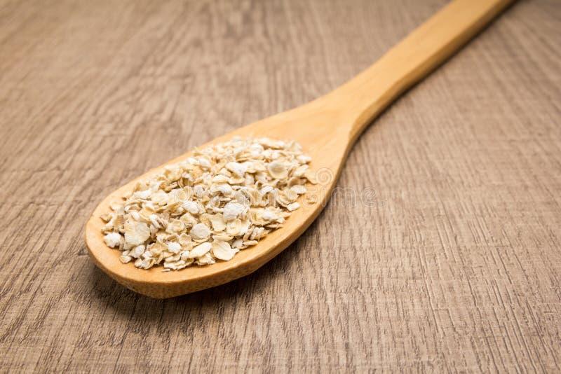 Chicco di grano dell'avena Cucchiaio e grani sopra la tavola di legno fotografia stock