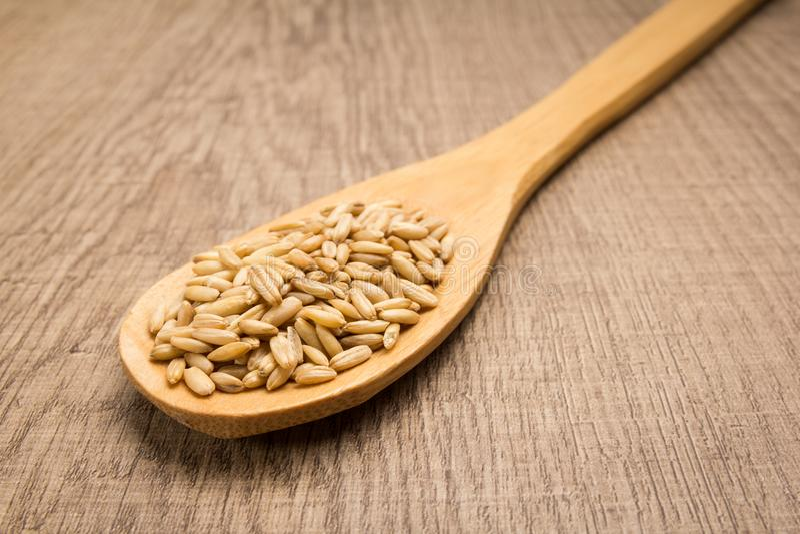 Chicco di grano dell'avena Cucchiaio e grani sopra la tavola di legno fotografia stock libera da diritti