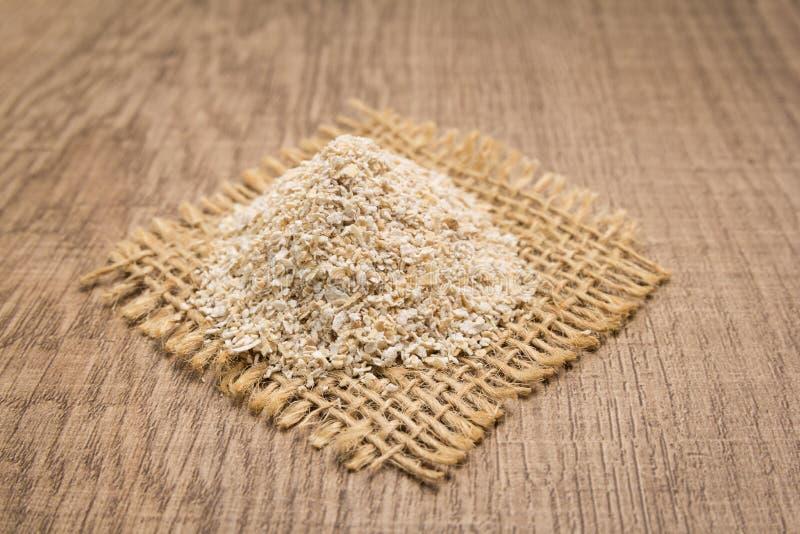 Chicco di grano dell'avena Grani su ritaglio quadrato di iuta Tabella di legno fotografia stock libera da diritti