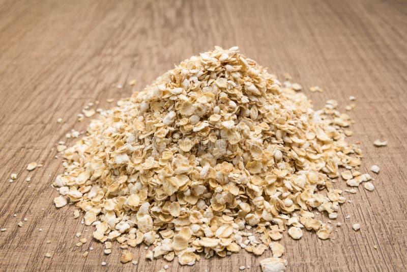 Chicco di grano dell'avena Mucchio dei grani sulla tavola di legno selettivo immagine stock libera da diritti