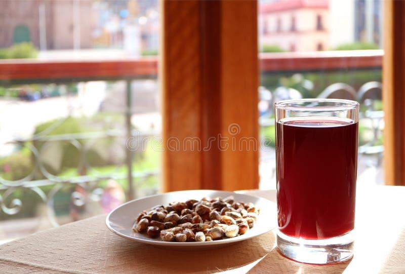 Chicha Morada, las bebidas tradicionales peruanas populares sirvió con una placa del maíz tostado andino imágenes de archivo libres de regalías