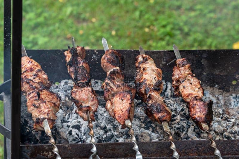 Chiche-kebab de Shashlik - barbecue géorgien traditionnel préparé Des chiches-kebabs sont grillés sur les charbons sur le vieux g photographie stock