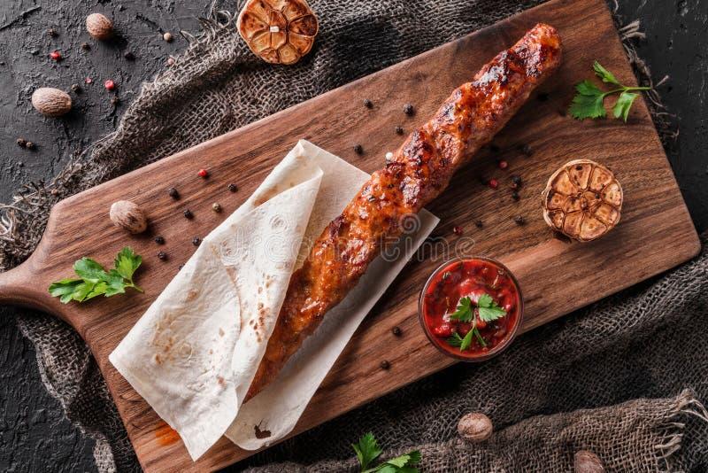 Chiche-kebab grillé de viande en pain pita avec la sauce tomate sur le panneau d'ardoise au-dessus du fond foncé Vue sup?rieure image libre de droits