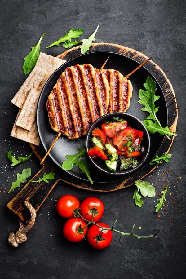 Chiche-kebab grillé juteux de lula de viande de poulet sur des brochettes avec de la salade de légume frais sur le fond noir image libre de droits
