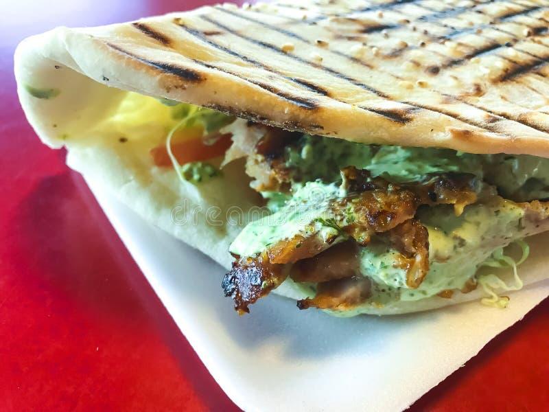 Chiche-kebab turc épicé de doner rempli de la viande rôtie, de salade fraîche et de sauce à ail en tortilla grillée photo libre de droits