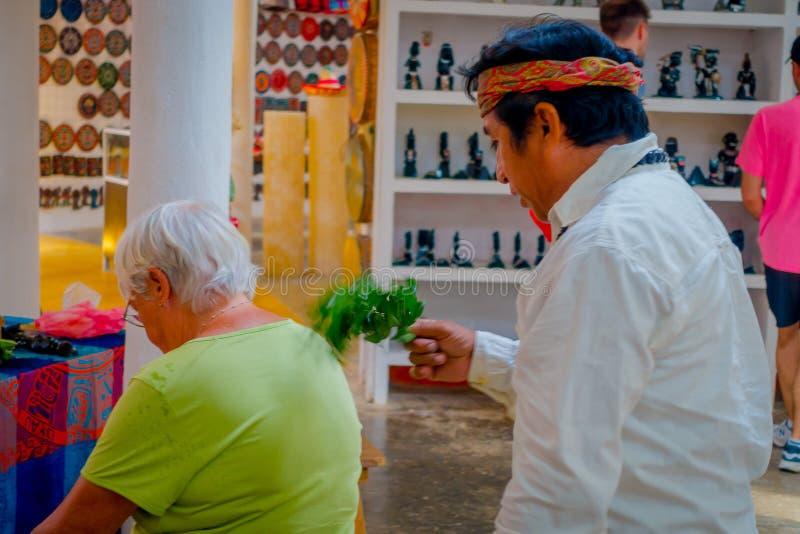 CHICHEN ITZA, MEXIKO - 12. NOVEMBER 2017: Schließen Sie oben vom indischen Chaman, der Anlagen verwendet, um eine alte Frau inner stockbild