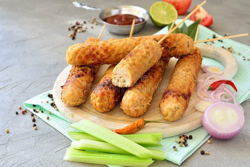 Chiches-kebabs sur un conseil avec la sauce tomate, épices, légumes, chaux images libres de droits