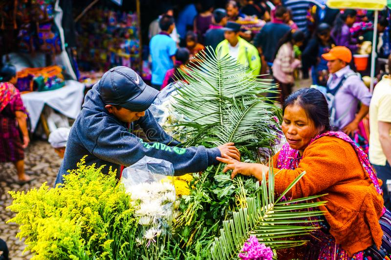 Chichicastenango, Guatemala on 2th May 2016: Indigneous woman with colorful clothes selling flowers on market in Chichicatenango stock photos