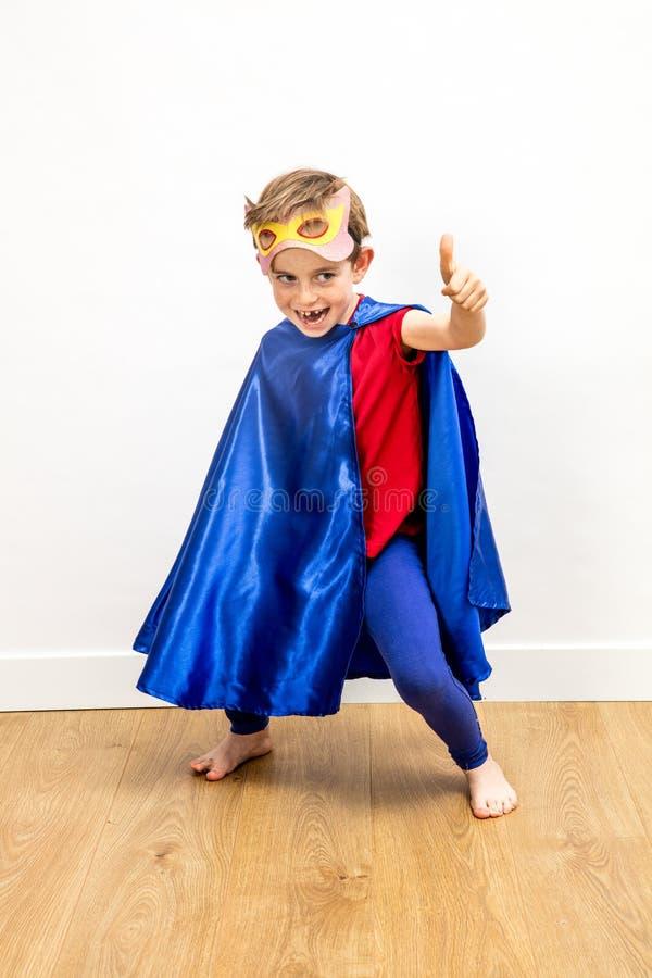Chichotliwa bohater chłopiec udaje super podniecającą władzę z aprobatami obrazy stock