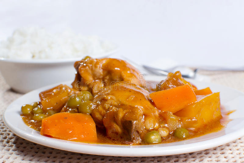 Chicken afritada with bowl of rice closeup stock image
