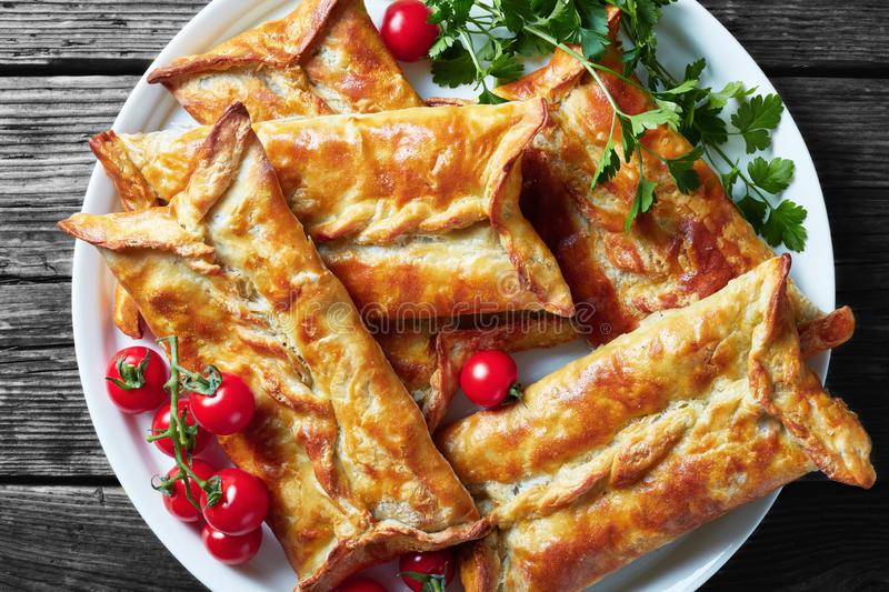 Chicken and baje sauce Stuffed Puff Pastry Borek. Baked Chicken Pies, Puff Pastry Chicken Bundles on a white plate with cherry tomatoes and parsley, view from royalty free stock photo