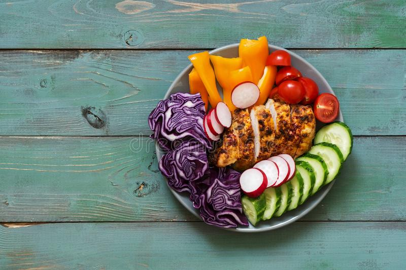Chicken baked with spices served in a plate with fresh vegetables, buddha bowl, green and blue rustic background. stock photography