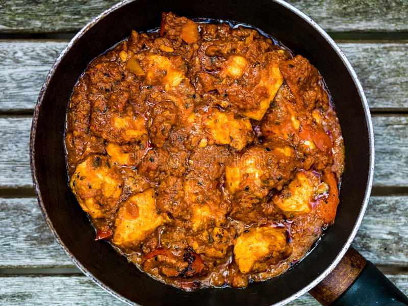 Chicken Balti Indian Curry Takeaway Meal Wth Pillau Rice. Against a Dark Wooden Background stock photography