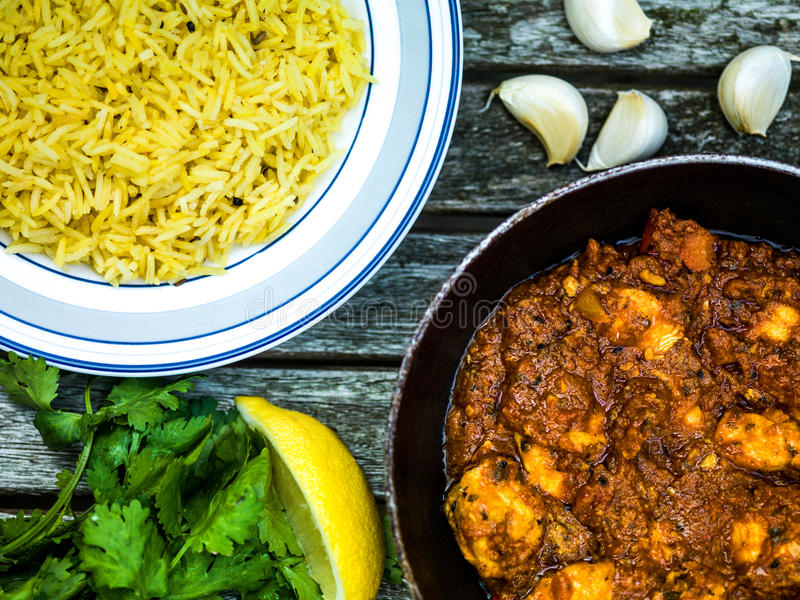 Chicken Balti Indian Curry Takeaway Meal Wth Pillau Rice. Against a Dark Wooden Background royalty free stock images