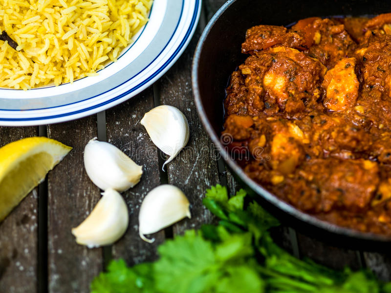 Chicken Balti Indian Curry Takeaway Meal Wth Pillau Rice. Against a Dark Wooden Background stock photo