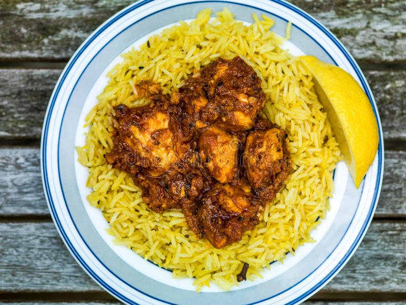 Chicken Balti Indian Curry Takeaway Meal Wth Pillau Rice. Against a Dark Wooden Background royalty free stock photo
