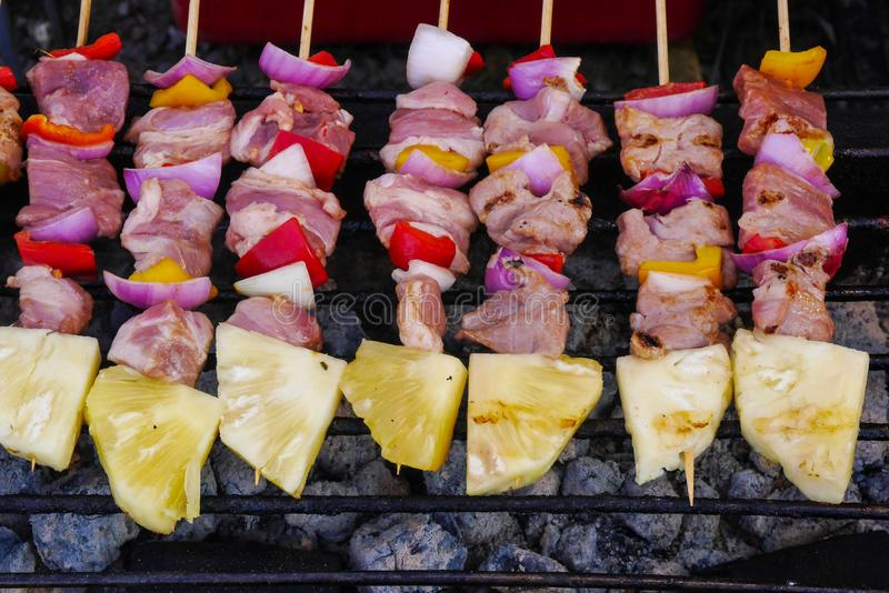 Chicken barbecues grilling on the portable grill with the heat from charcoals royalty free stock photography