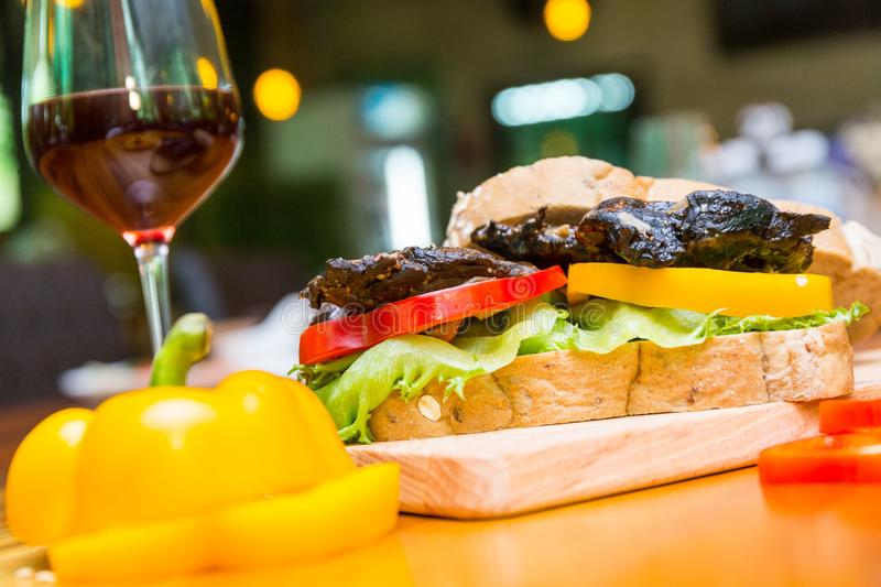 Chicken berger on table. Chicken berger and wine on wood dish stock image