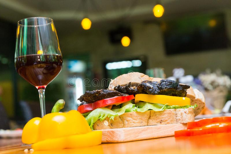 Chicken berger on table. Chicken berger and wine on wood dish stock photo