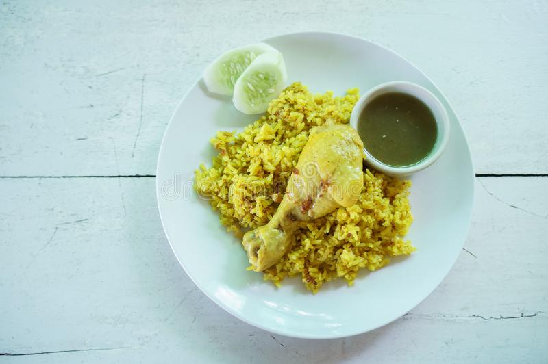 Chicken biryani chicken rice curry with coconut with spicy sauces. On white dish in vintage white wooden table. For food stock images